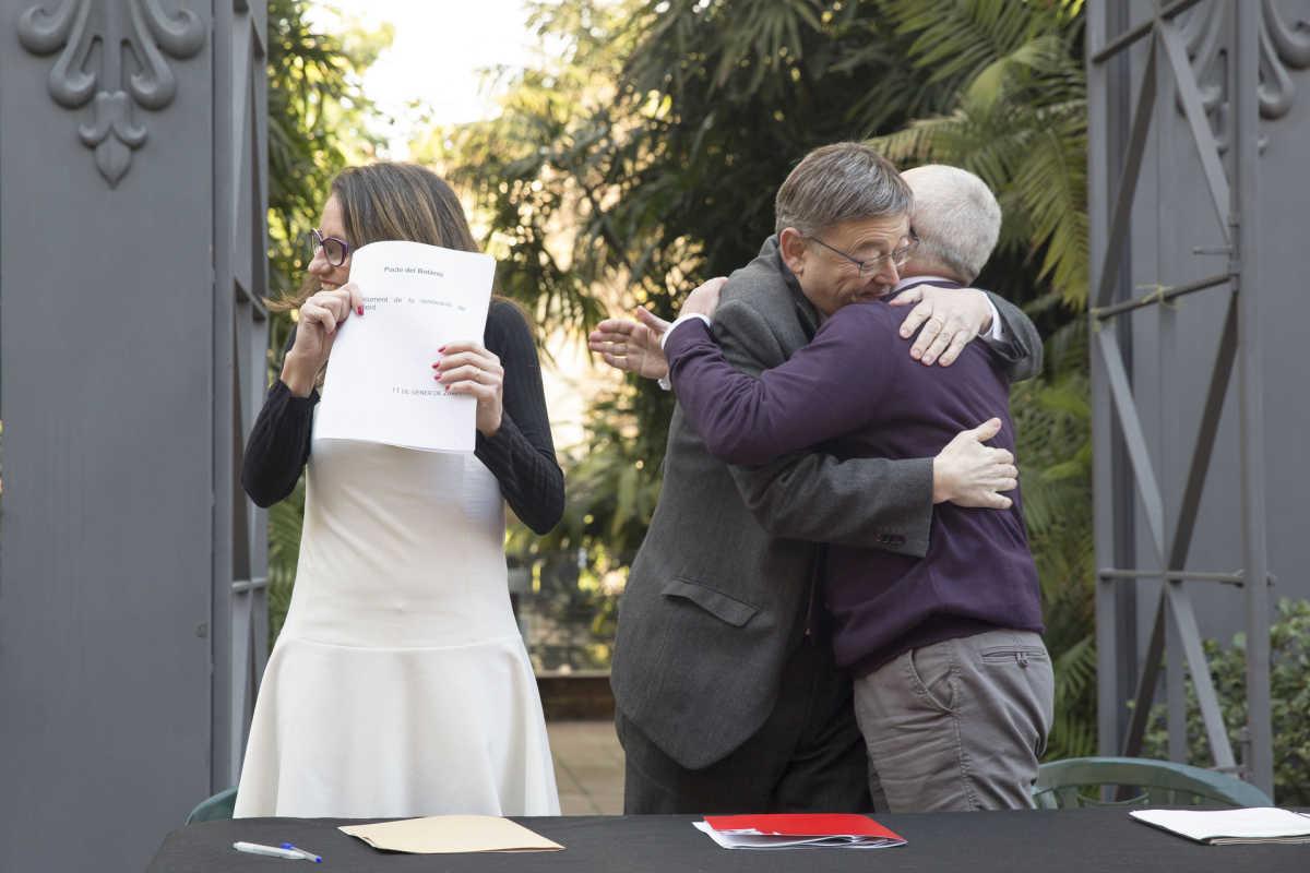 Puig y Montiel se abrazan tras la renovación del Pacto del Botánico mientras Oltra muestra el documento. Foto: EVA MÁÑEZ