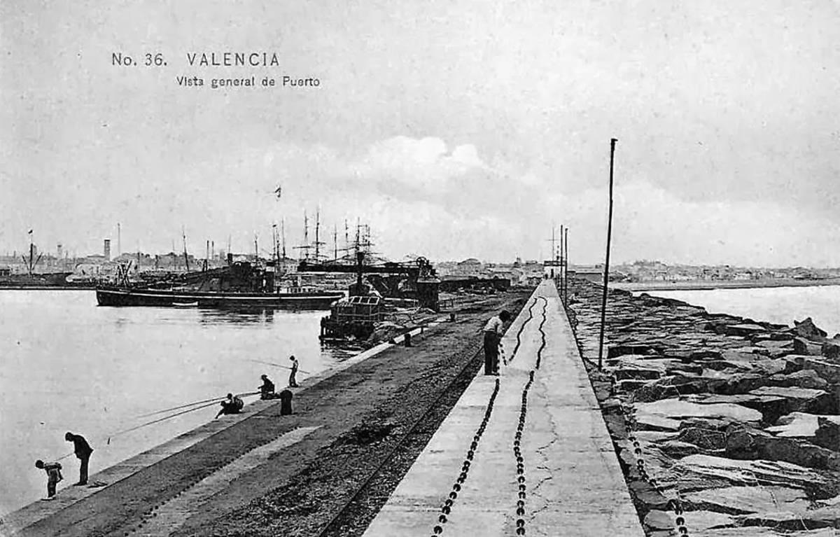 Obres de construcció de l'escullera nord que acabaria portant al vell far. Al fons, a l'esquerra, el campanar del Rosari, a la dreta, la platja.