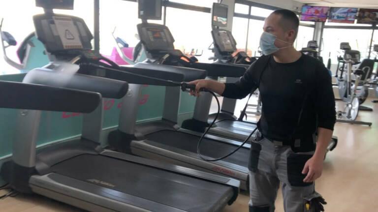 Un trabajador desinfecta las máquinas deportivas del gimnasio Atalanta. Foto: GIMNASIO ATALANTA